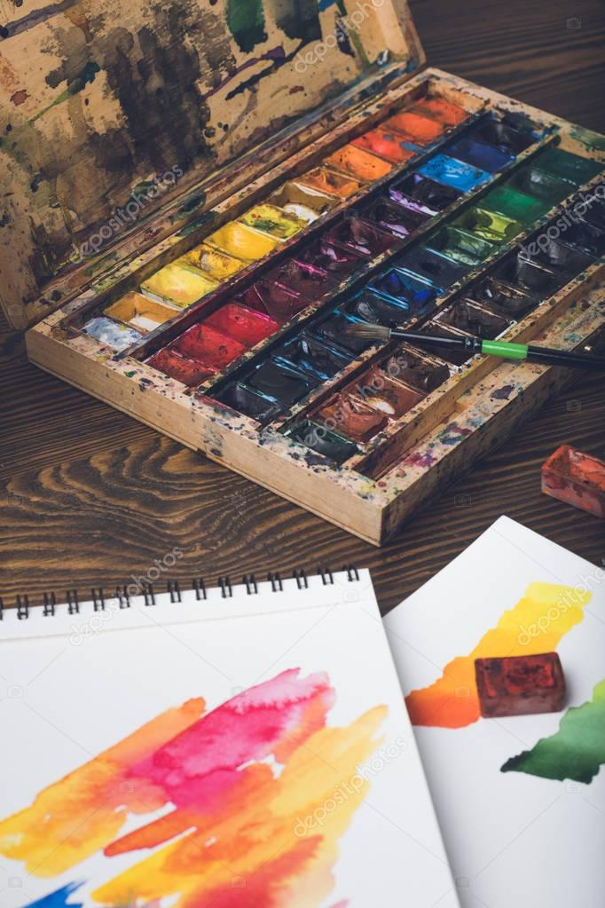 close-up view of watercolor paints, paintbrush and abstract sketches at designer workplace