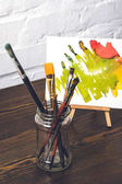 close-up view of various paint brushes in glass and abstract painting behind at designer workplace