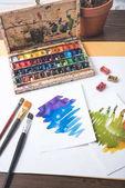 Draufsicht auf Farben, Pinsel und Aquarellskizzen am Designerarbeitsplatz
