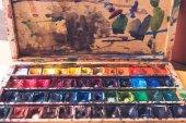 Nahaufnahme von Aquarellfarben in chaotisch Behälter mit Pinselstrichen und Flecken