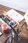 Selektive Fokussierung von Aquarellfarben und Pinseln am Designerarbeitsplatz