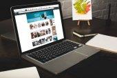 Nahaufnahme des Designer-Arbeitsplatzes mit Notebooks und Laptop mit Amazon-Website auf dem Bildschirm
