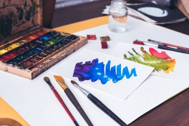 close-up view of watercolor paints, paintbrushes and abstract sketches at designer workplace
