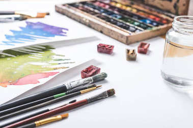 close-up view of paints, paintbrushes and watercolor sketches at designer workplace
