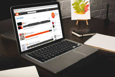 close-up view of designer workplace with notebooks and laptop with soundcloud website on screen