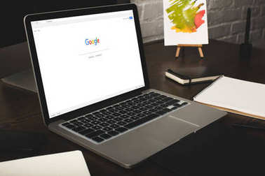 designer workplace with laptop and google website on screen