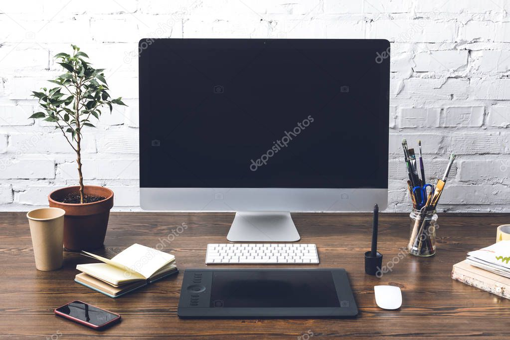 desktop computer with blank screen and digital devices at designer workplace