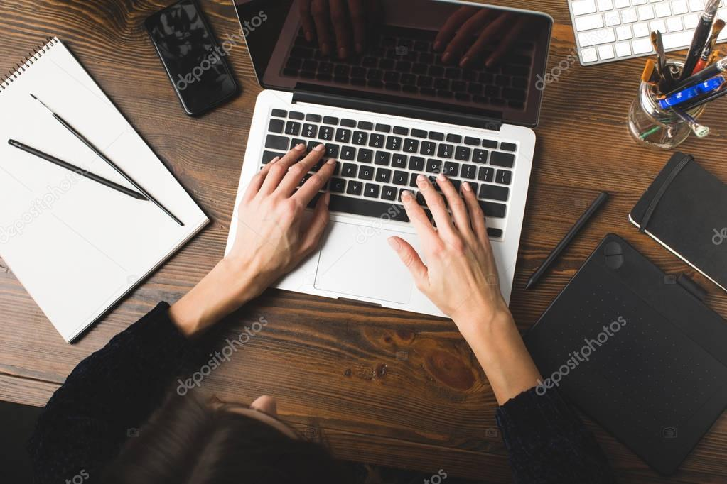 top view of designer using laptop and working with graphics tablet