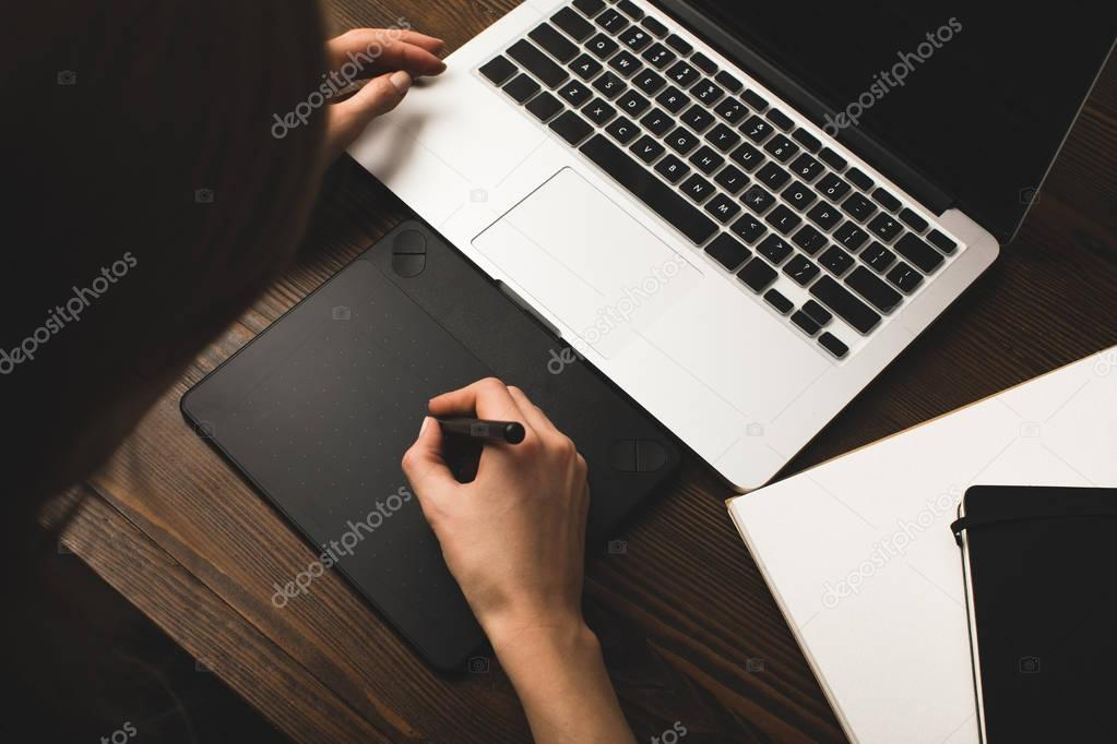 cropped shot of person using laptop and graphics tablet