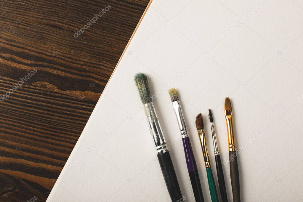 top view of paint brushes and blank drawing album on wooden table