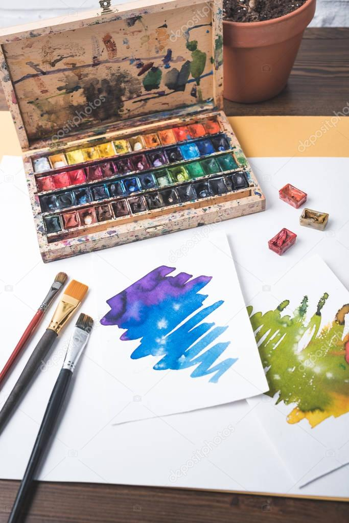 top view of paints, paintbrushes and watercolor sketches at designer workplace