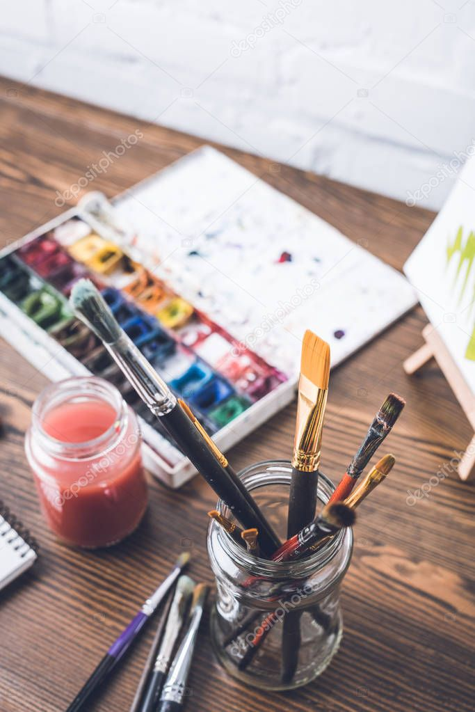 selective focus of watercolor paints and paintbrushes at designer workplace