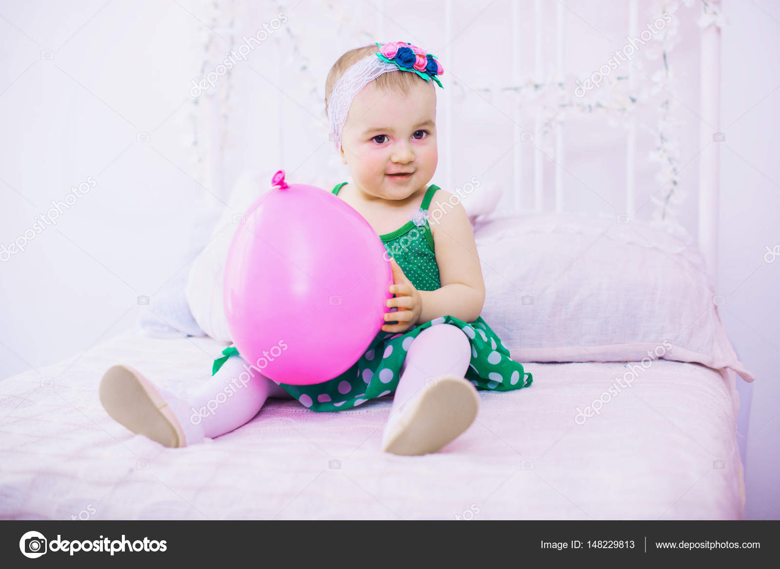 Cute baby girl 1 year old sitting on bed with pink balloon in room