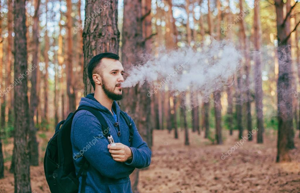 Vaping. Casual men with beard vaping an electronic cigarette. Vaping outdoors in forest. Safe smoking. Young vaper.