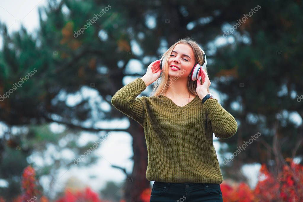 Happy girl dancing and listening to the music on nature in autumn