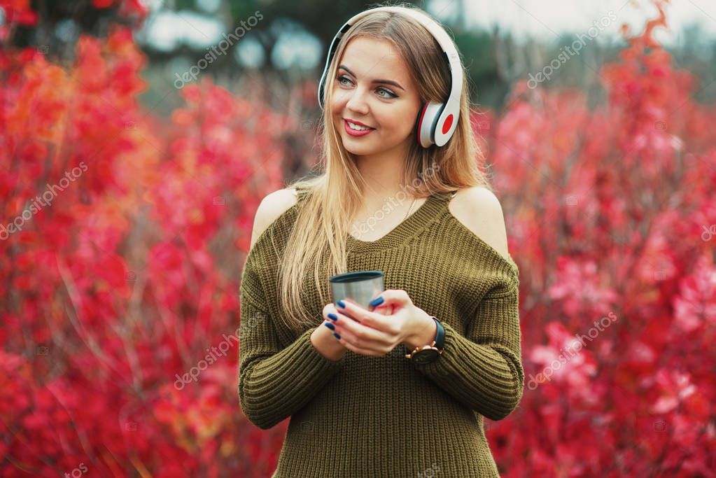 Beauty teenage girl with cup of tea, headphones and smartphone smiling standing outdoors in park