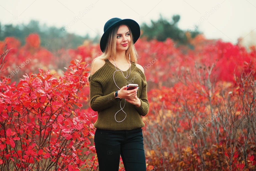 young hipster stylish beautiful girl listening to music, mobile phone, headphones, enjoying, denim outfit, smiling, happy, cool accessories, vintage style, having fun, laughing, park