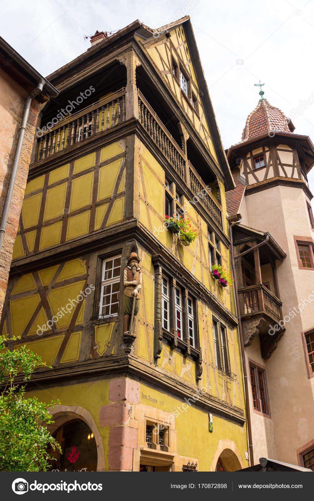 Antigua casa con entramado de madera y un edificio con gran torre en ...