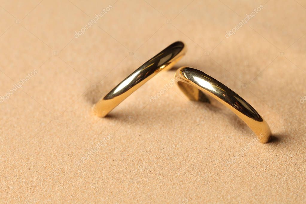 Wedding rings in sand on the beach