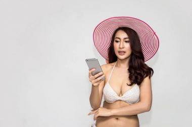 Beautiful girl in swimsuit playing mobile phone.