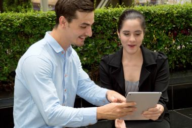 Young business people are interested in playing tablet.