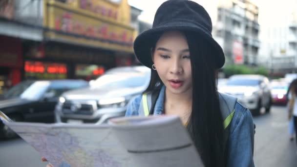 Cestovní koncept. Krásné dívky čtou mapu na kraji silnice. Rozlišení 4k.