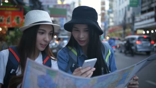 Travel concept. Beautiful girls are reading the map on the roadside. 4k Resolution.