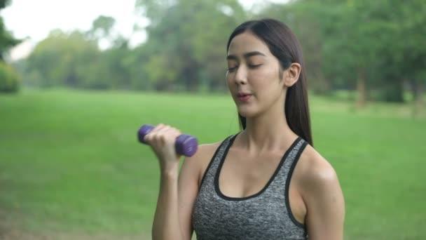 Cvičení pojmů. Krásné ženy cvičí vybudovat silné svaly v zahradě. Rozlišení 4k.