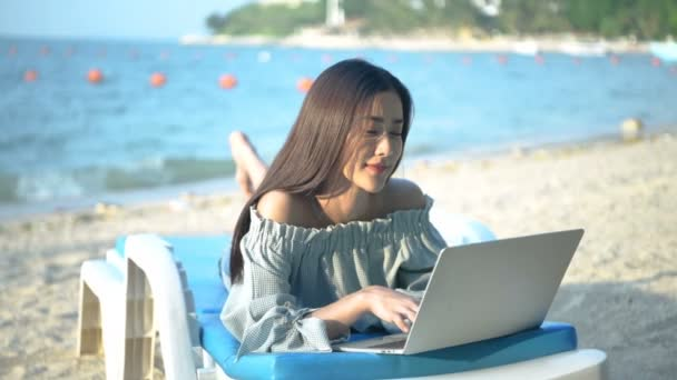 Holiday concept. A beautiful woman is working with a notebook on the beach. 4k Resolution.