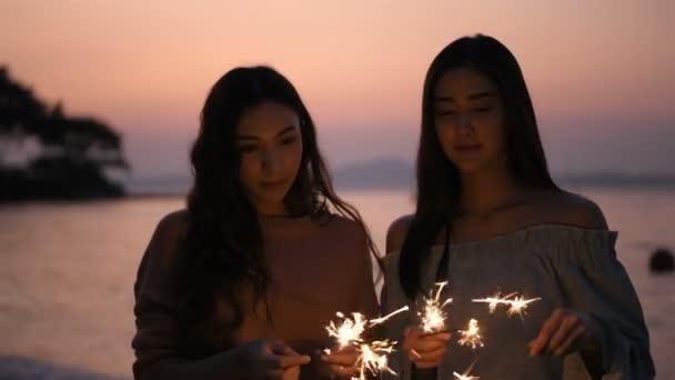 Urlaubskonzept. Das Mädchen spielt fröhlich mit Feuerwerk am Strand. 4k-Auflösung.