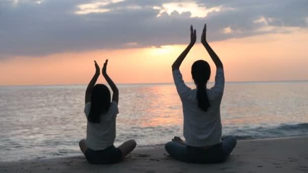 Silueta matky a dcery, jak večer cvičí jógu u moře. Rozlišení 4k.