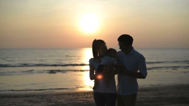 Urlaubskonzept. Vater und Mutter zeigen am Strand ihre Liebe zu Kindern. 4k-Auflösung.