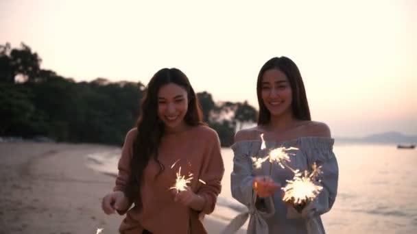 Ünnepi ötlet. A lány boldogan játszik tűzijátékkal a parton. 4k felbontás.
