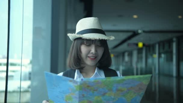 Koncept cestovního ruchu. Krásné dívky cestují s pomocí mapy hledat turistické atrakce. Rozlišení 4k.