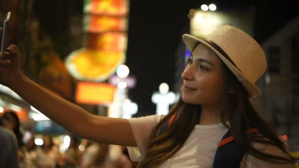 Reisekonzept. Ein schönes Mädchen fotografiert nachts in der Fußgängerzone. 4k-Auflösung.