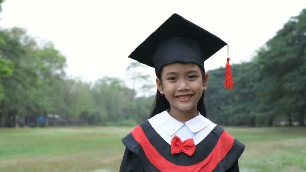 Vzdělávací pojmy. Dívka v maturitních šatech stojí sebevědomě na zahradě. Rozlišení 4k.
