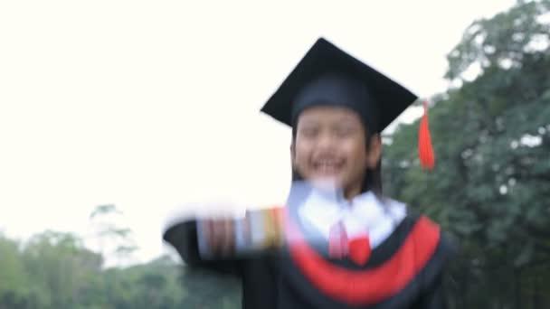 Vzdělávací pojmy. Dívka v maturitních šatech je na zahradě šťastná. Rozlišení 4k.