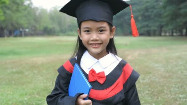 Vzdělávací pojmy. Dívka v maturitních šatech chodí sebevědomě. Rozlišení 4k.