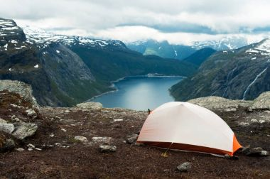 Tent on mountain cliff edge trolltunga stock vector
