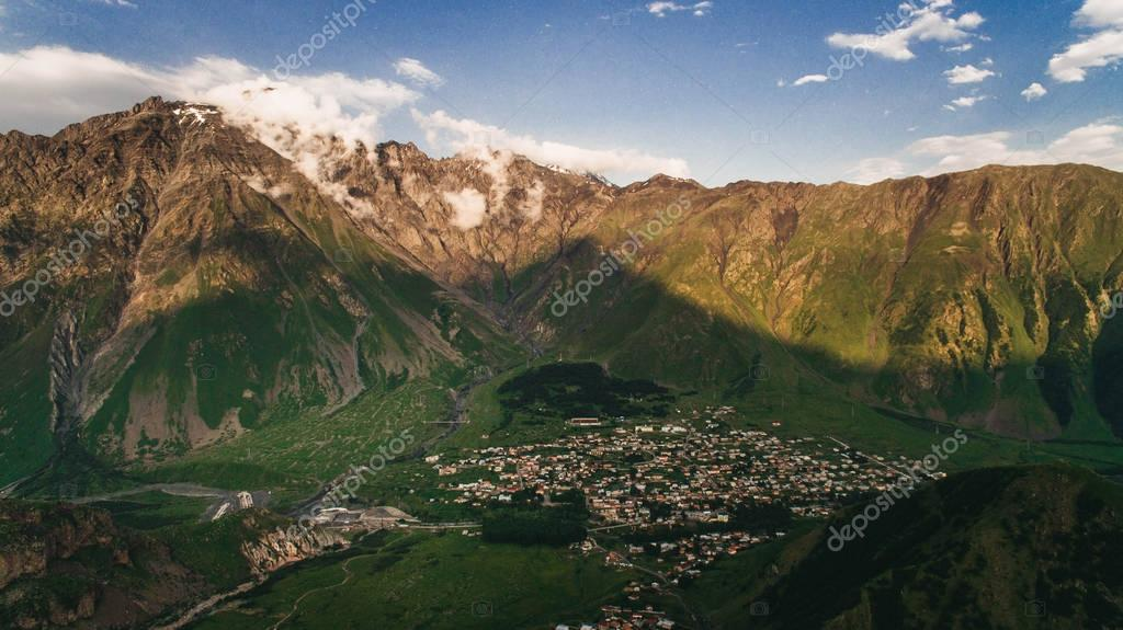 city in mountains with cloudy sky