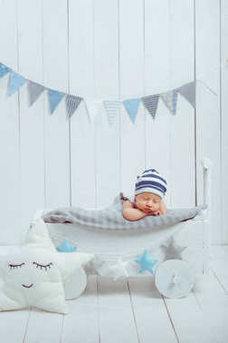 portrait of adorable infant baby in hat sleeping in wooden baby cot decorated with stars