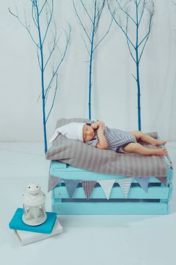 adorable newborn baby in bodysuit and hat sleeping on wooden box with lantern near by
