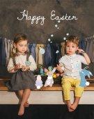 stylische kleine Kinder mit Korb voller Ostereier vor rustikalem Girlanden, fröhlichen Osteraufschriften und Hasen-Collage