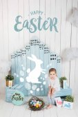 Photo adorable little child sitting in easter decorated room with happy easter lettering