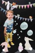 Fotografia bambino adorabile con le orecchie del coniglietto e garland sorride alla macchina fotografica su nero, felice lettering di Pasqua in collage bolle e coniglietti