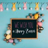 vista superiore di Pasqua variopinte uova e vi auguriamo felice della lavagna lettering di Pasqua sulla superficie blu