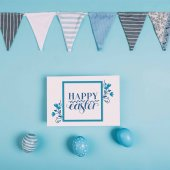 Fotografie top view of greeting card with happy easter lettering and easter eggs on blue surface