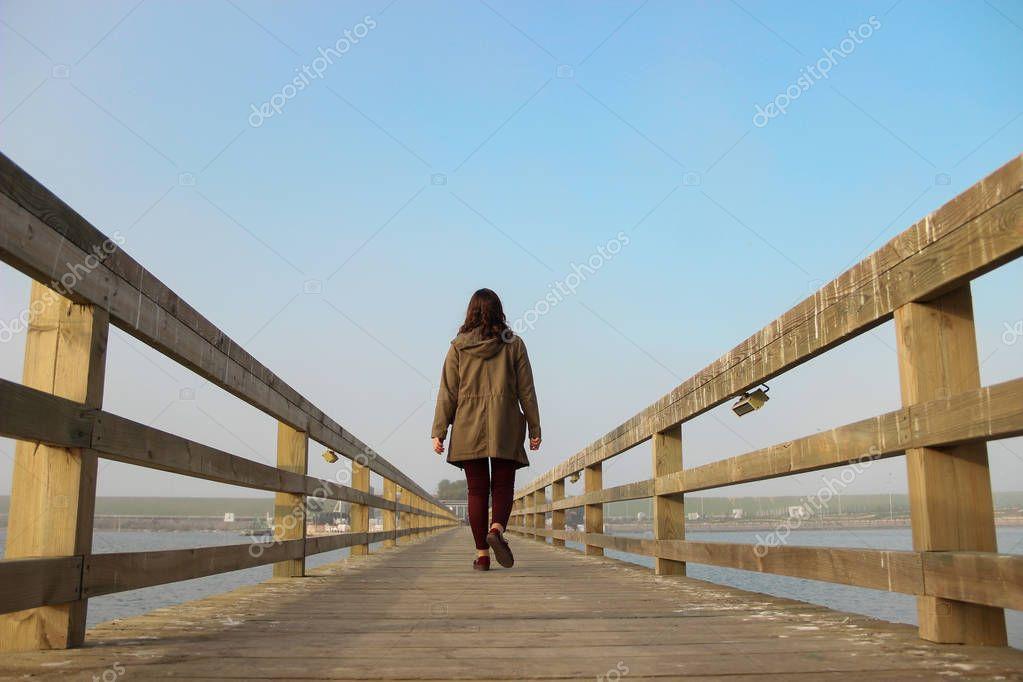 A girl walking on a wooden bridge