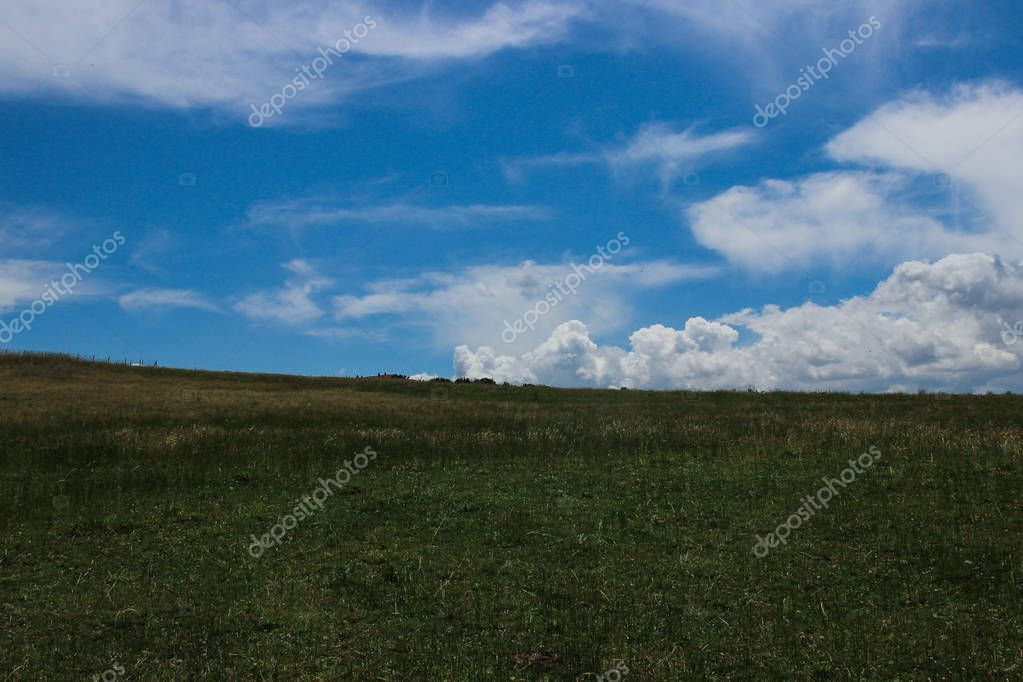 White clouds in blue sky and green hill.