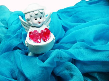 angel toy holding crystal heart in hands on silky background